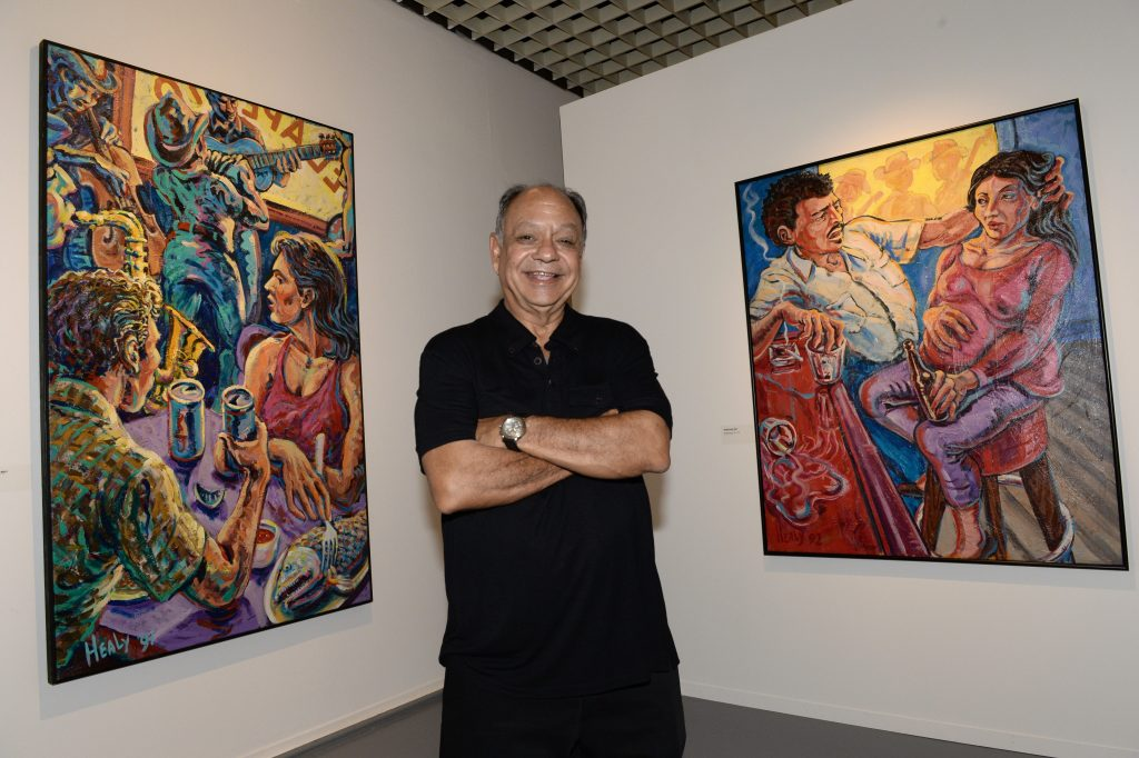 Cheech Marin poses in front of a painting by US artist Wayne Alaniz Healy on June 26, 2014 at the Aquitaine museum in Bordeaux. Photo by Mehdi Fedouach/AFP via Getty Images.